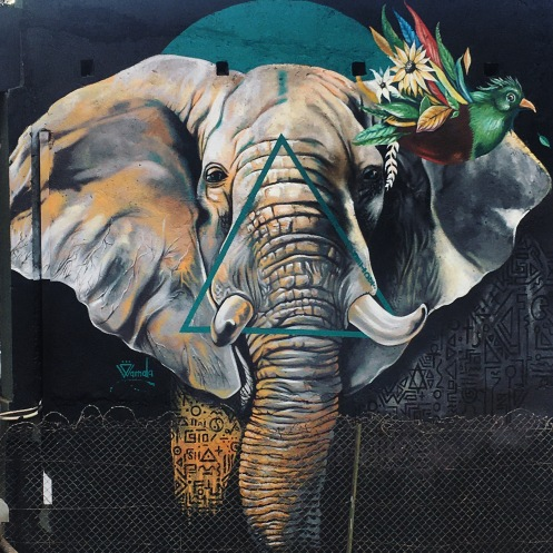A mural of an elephant with a bouquet of flowers behind one ear