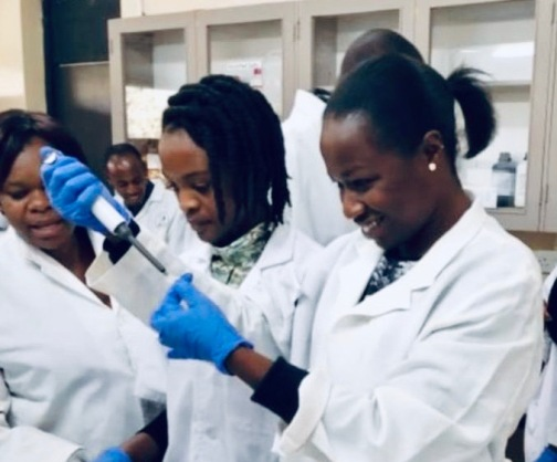 A Kenyan woman in a white lab coat and blue gloves scrapes a sample off a microscope slide