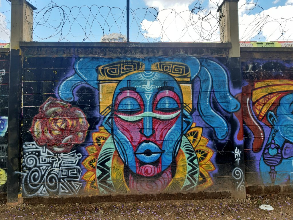A mural of a colorful blue and pink face on a cement wall